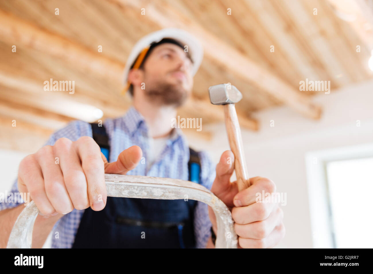 Close-up portrait of a handyman with a hammer in his hands, standing on the ladder, unfocused - Stock Image