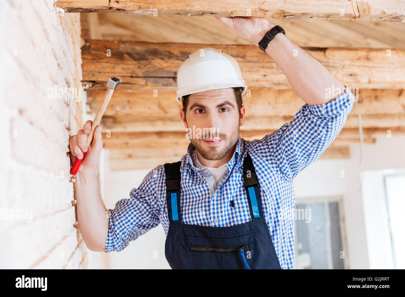Close-up portrait of a handsome young builder holding a hammer - Stock Image