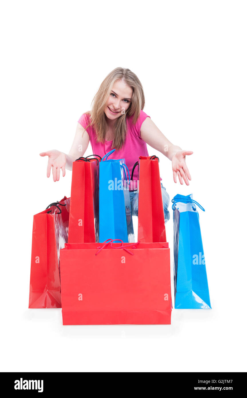 Consumerism and sale concept with cheerful woman showing colorful shopping bags isolated on white background with - Stock Image