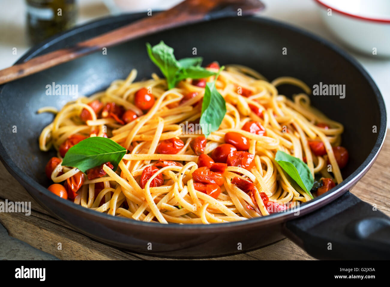 Freshly cooked  Fettuccine with cherry tomatoes in a sauce pan Stock Photo