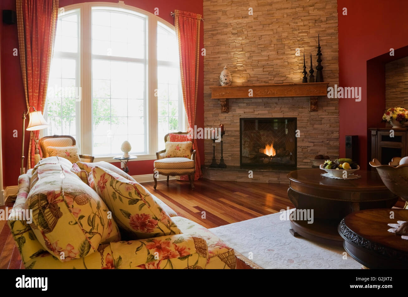 living room flowery upholstered sofa chairs lit gas fireplace inside