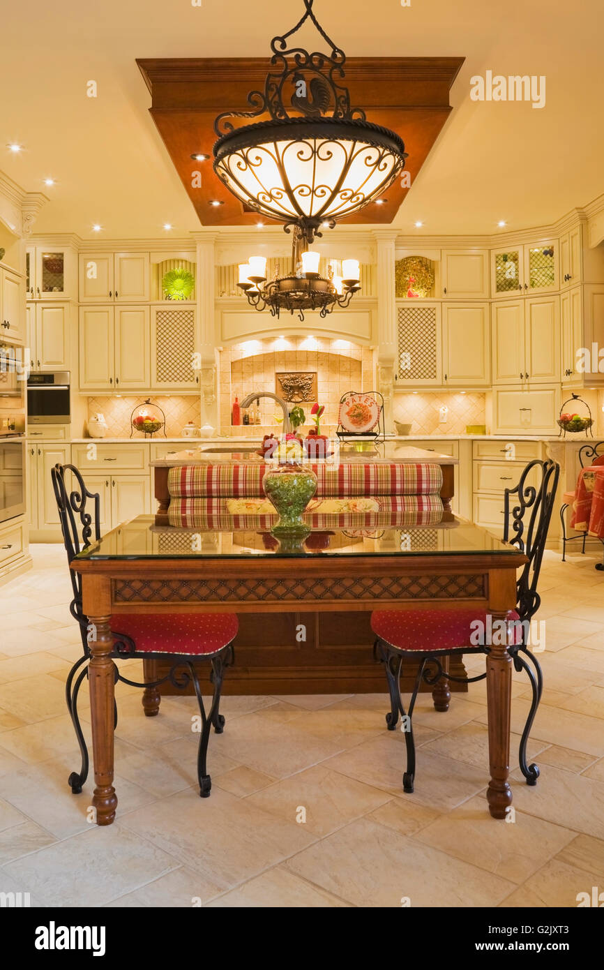 illuminated chandeliers above breakfast table red upholstered chairs rh alamy com  cottage style upholstered furniture