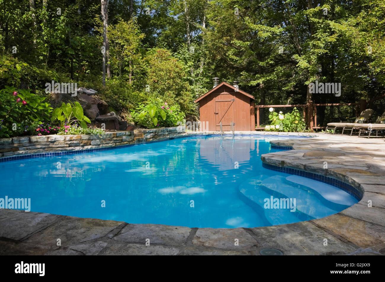 Inground swimming pool waterfall flagstone decking in ...
