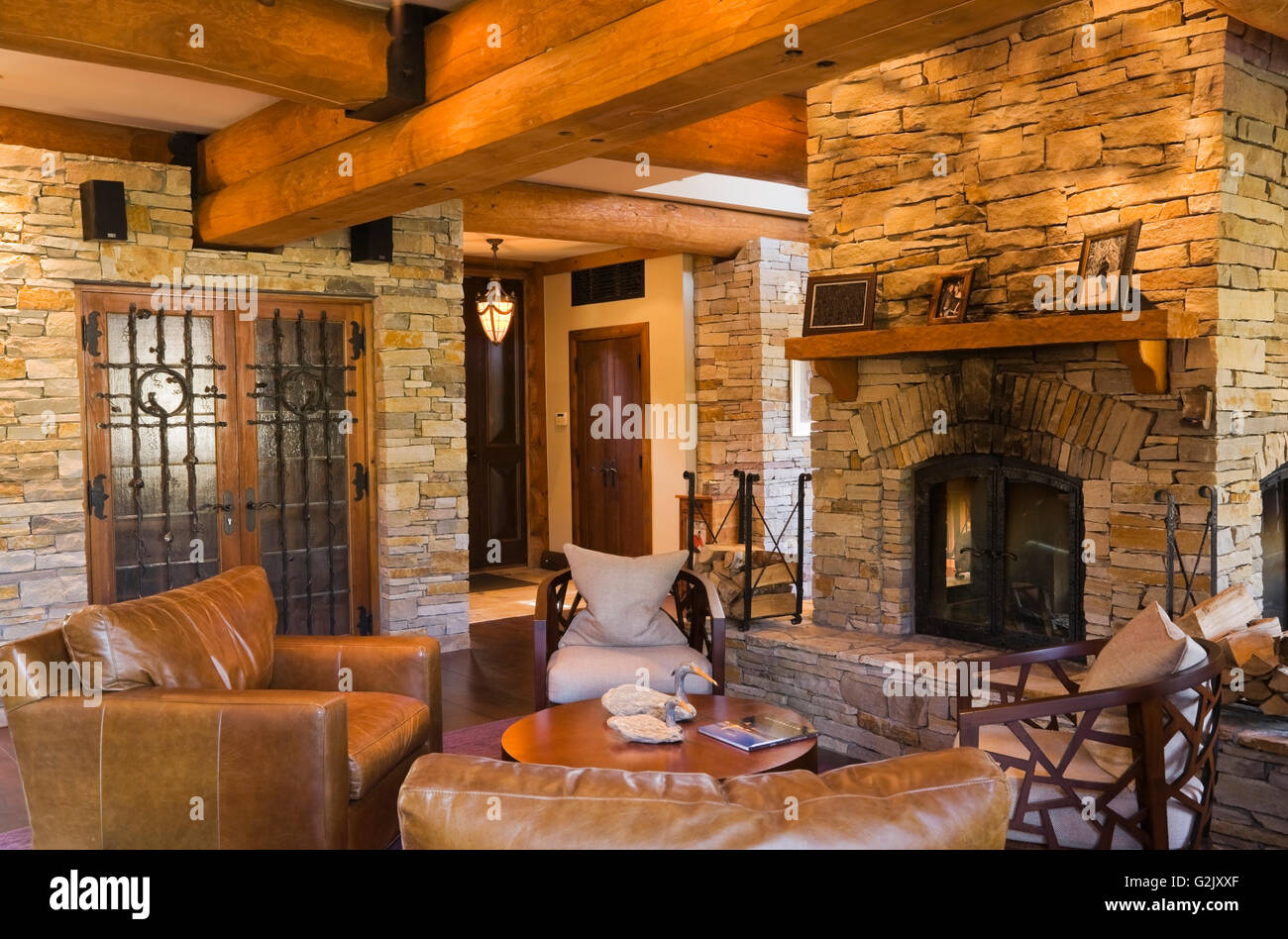 Leather chairs next four sided natural stone fireplace wine cellar french doors natural stone contour in living room inside a