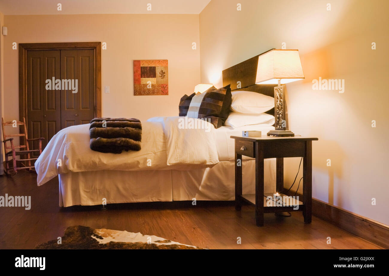 Guest bedroom brown white animal hide skin rug king size bed in basement inside a luxurious cottage style log home - Stock Image