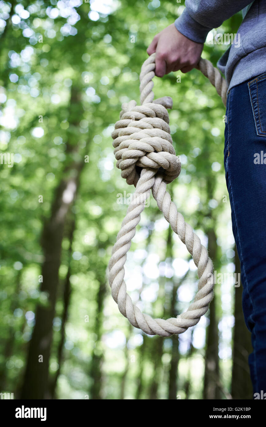 Depressed Man Contemplating Suicide By Hanging In Forest - Stock Image