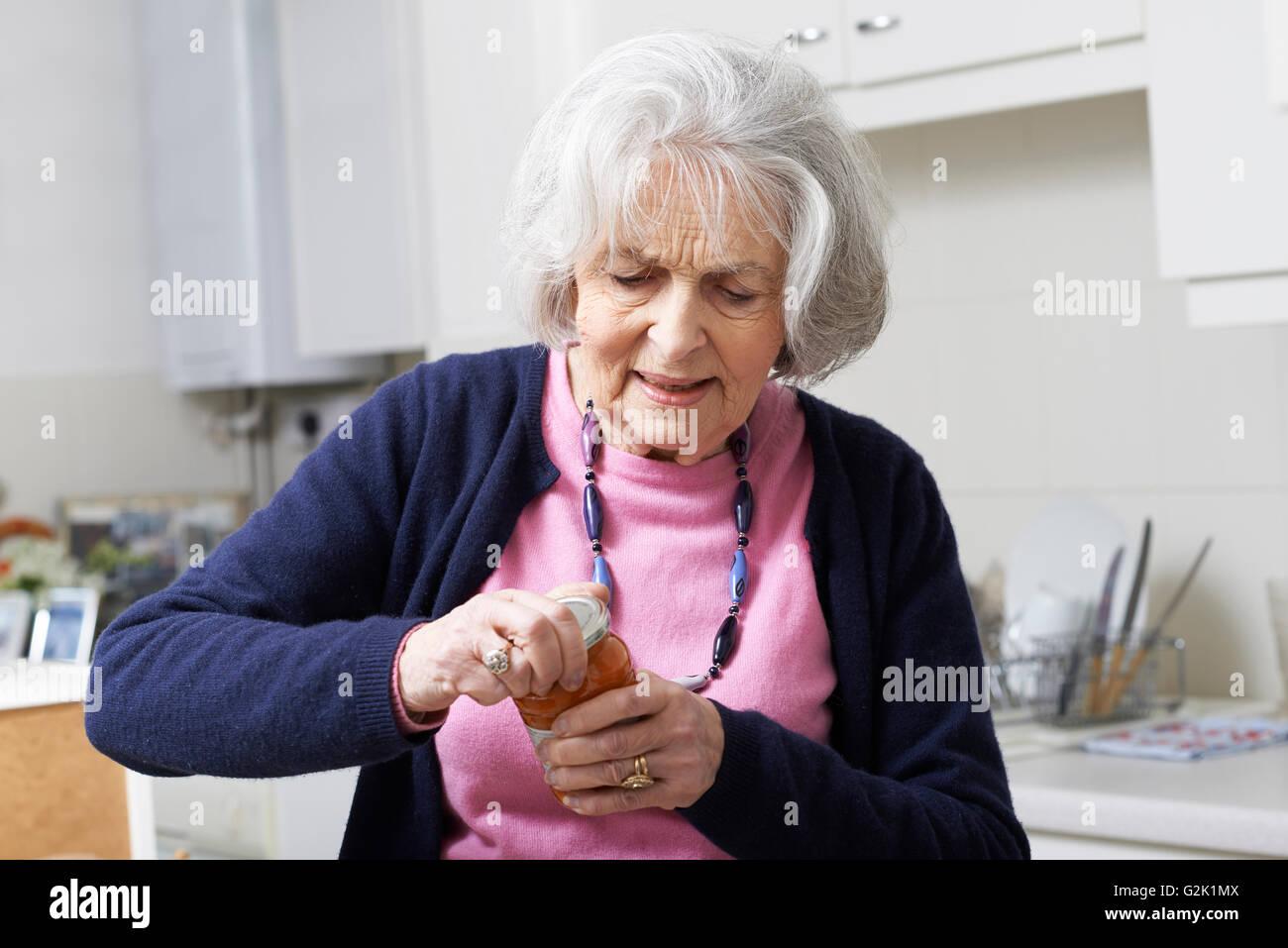 Senior Woman Struggling To Take Lid Off Jar - Stock Image