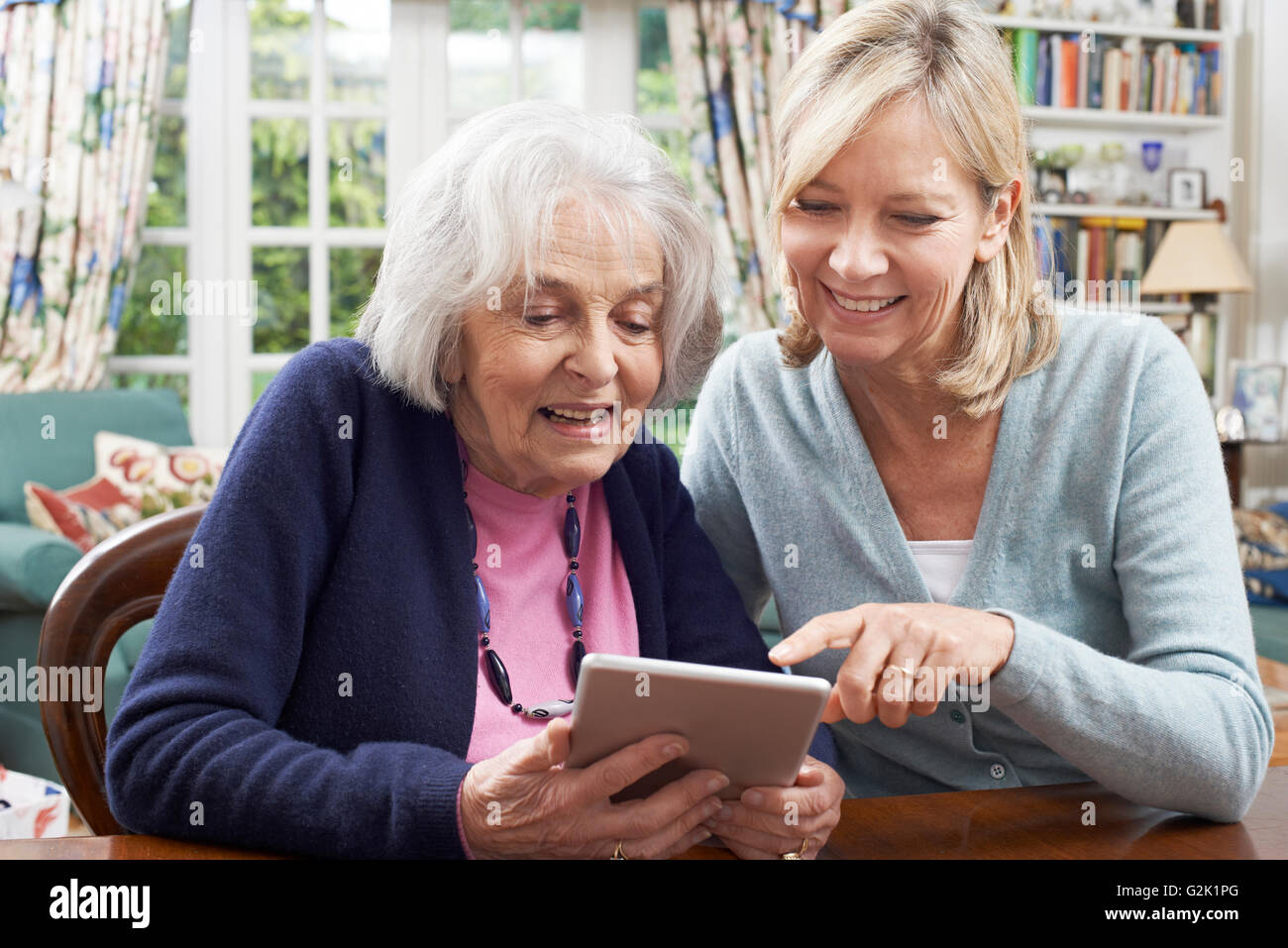 Female Neighbor Showing Senior Woman How To Use Digital Tablet Stock Photo