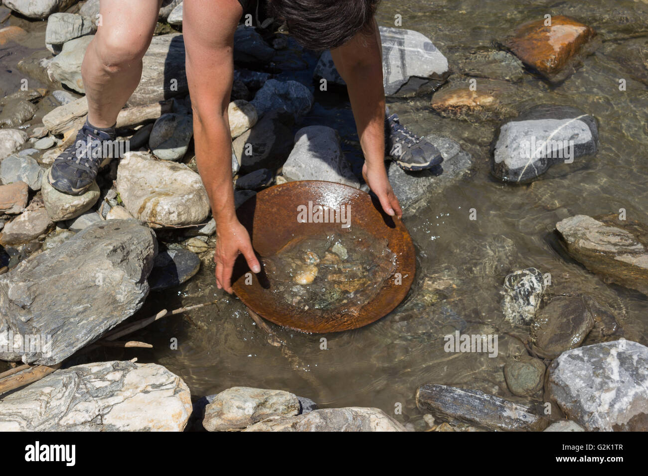 woman Panning for Alluvial Gold, using the traditional panning method - Stock Image