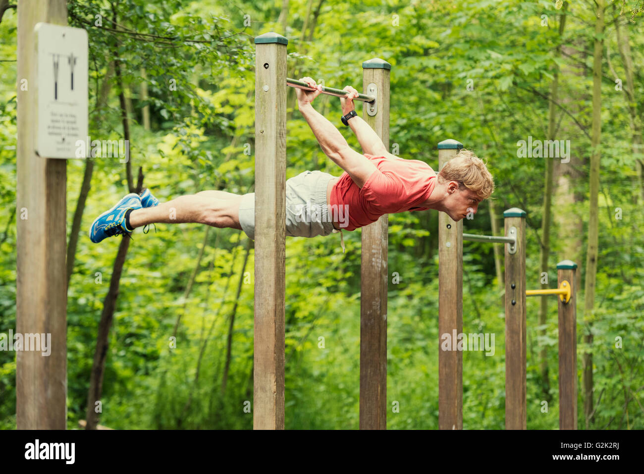 Male athlete doing muscle-up on horizontal bar - Stock Image