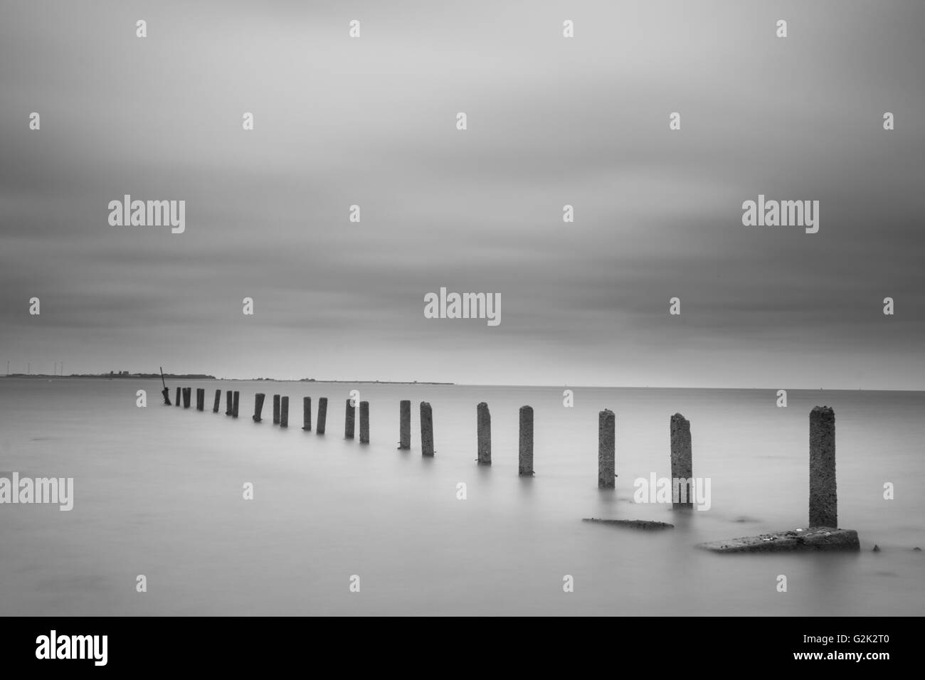 High key black and white image of old pier pylons on the Suffolk beach of Clackton. - Stock Image