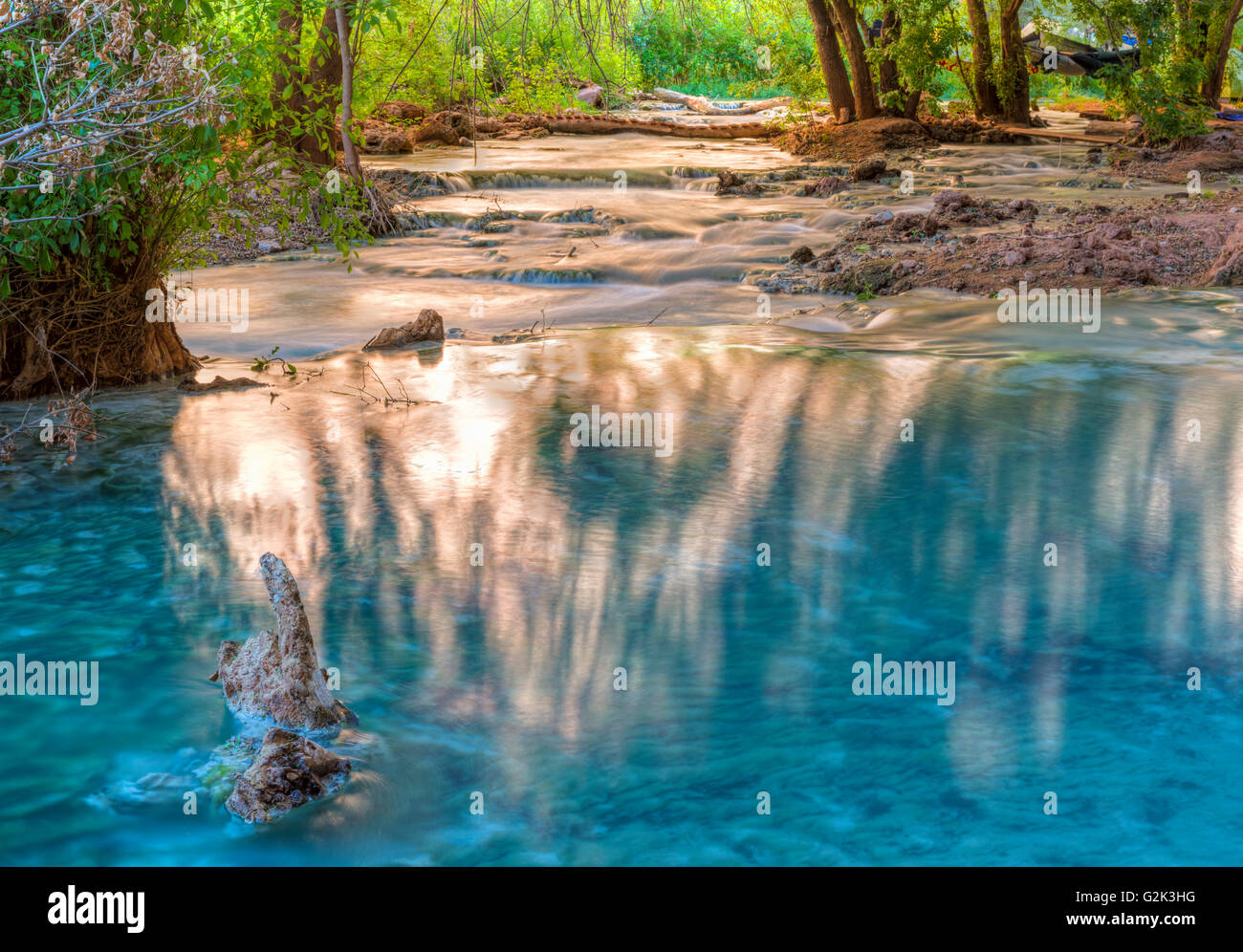 Sunlight bounces off the cliffs and lights up reflections in Havasu Creek on Havasupai Indian Reservation in the - Stock Image