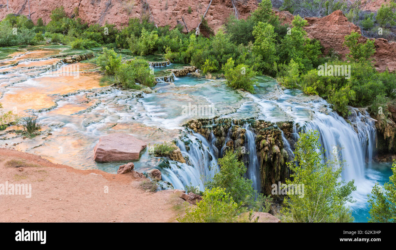 The morning sun bounces of the red cliffs and reflects off the travertine pools of Little Navajo Falls in Havasu - Stock Image