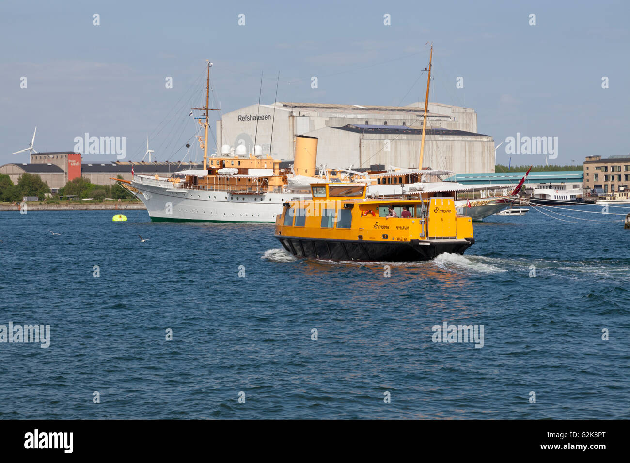 A yellow harbour bus passing the anchored Danish Royal Yacht HDMY Dannebrog at Holmen in the harbour of Copenhagen. - Stock Image