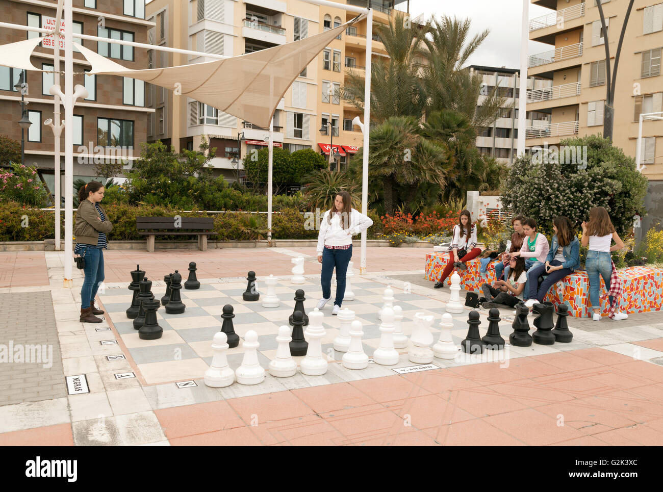 Spanish teenage girls playing  chess on a giant chessboard in the street, Estepona, Andalusia, Spain Europe - Stock Image