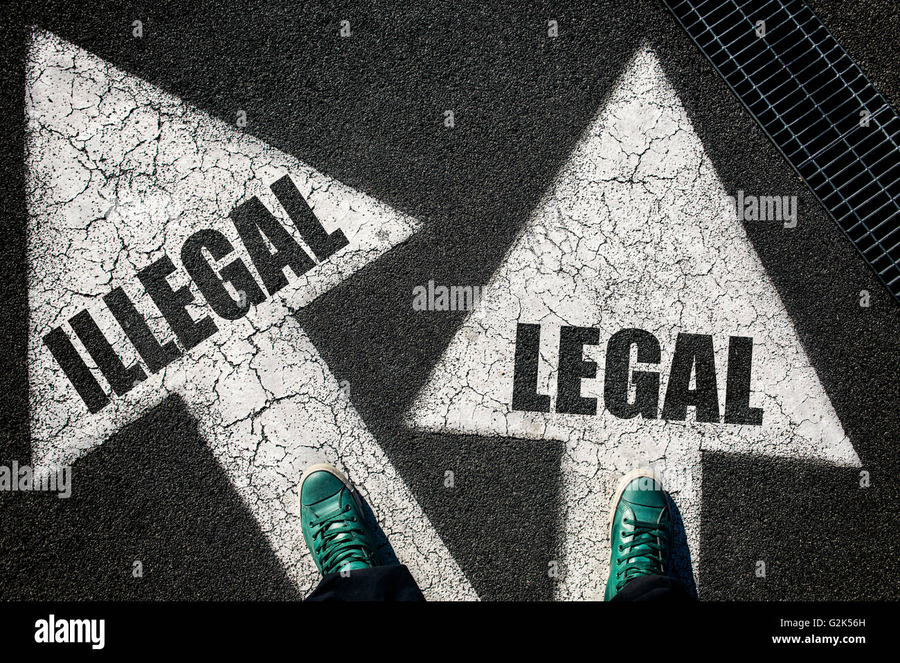 Dilemma concept with mans legs on legal and illegal signs on the road - Stock Image