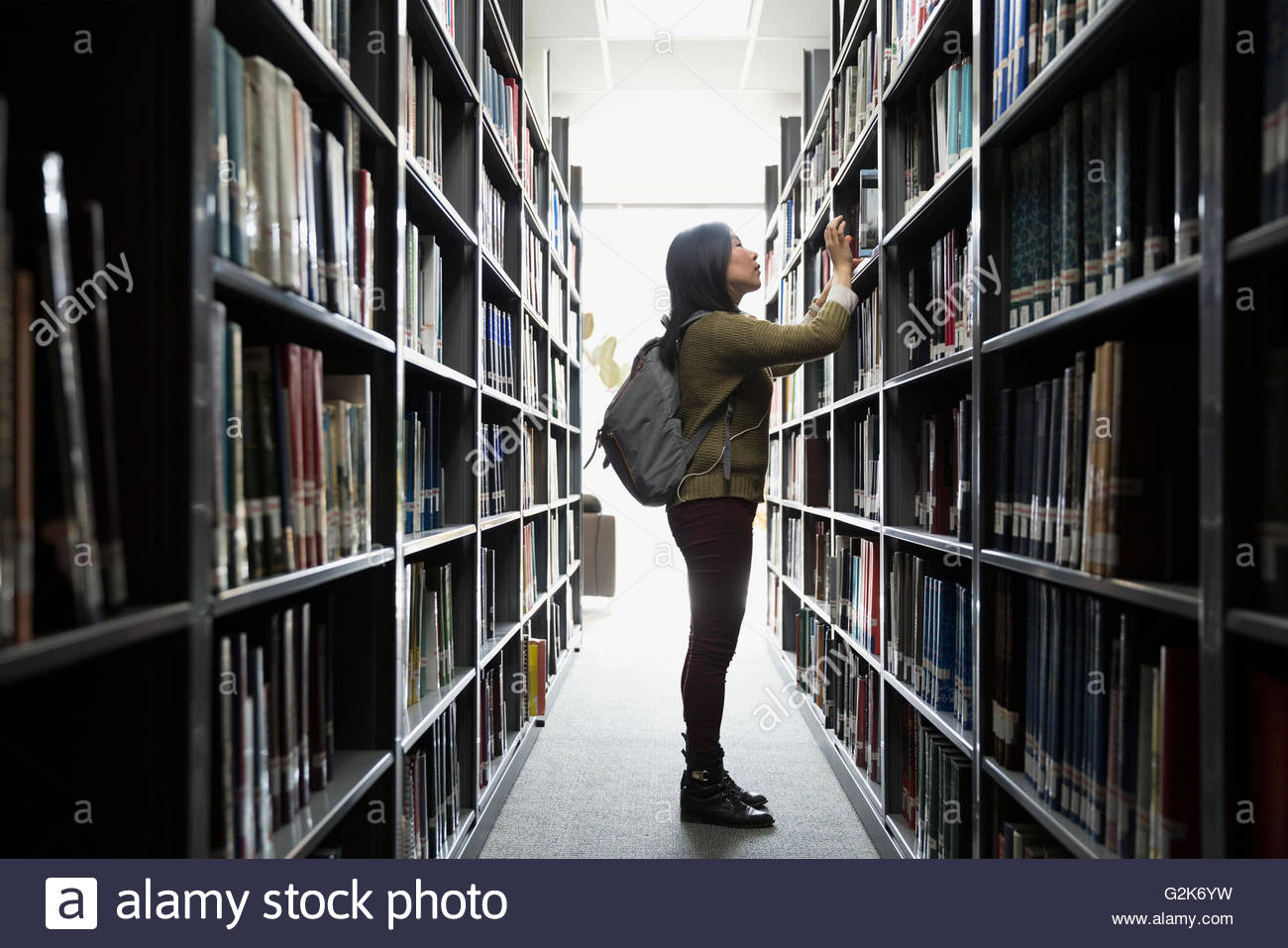 College student searching for book in library - Stock Image