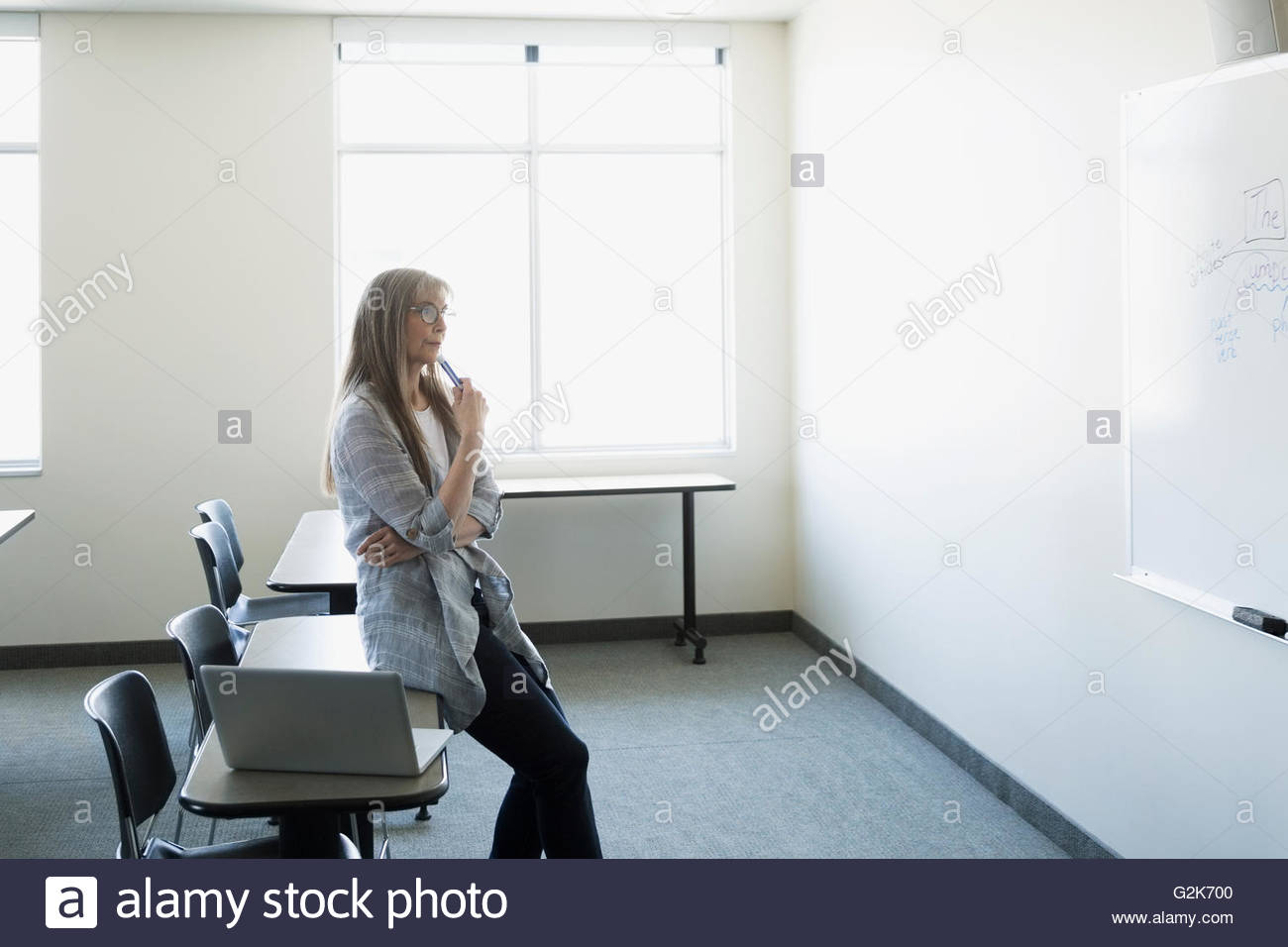Pensive professor with laptop looking at whiteboard in classroom - Stock Image