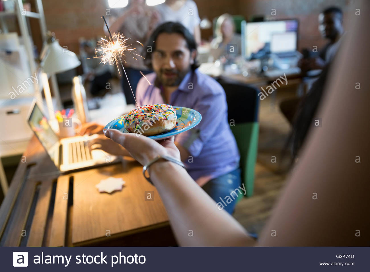 Coworker serving creative businessman birthday donut with sparkler - Stock Image