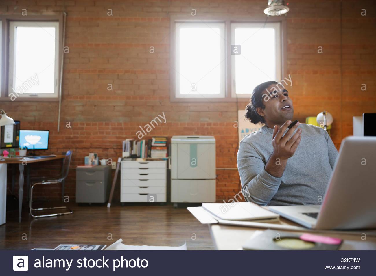 Designer talking at laptop in office - Stock Image
