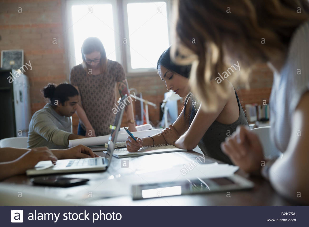 Designers working at laptop and on proofs in office - Stock Image