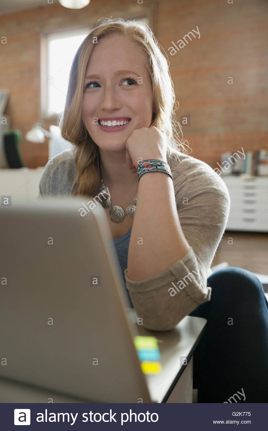 Smiling female designer using laptop looking away - Stock Image