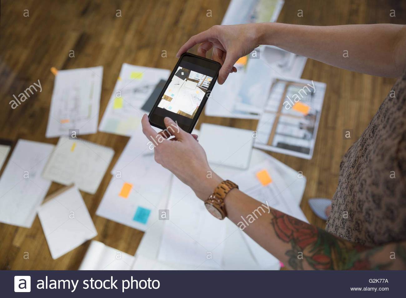 Designer photographing proofs and paperwork with camera phone - Stock Image