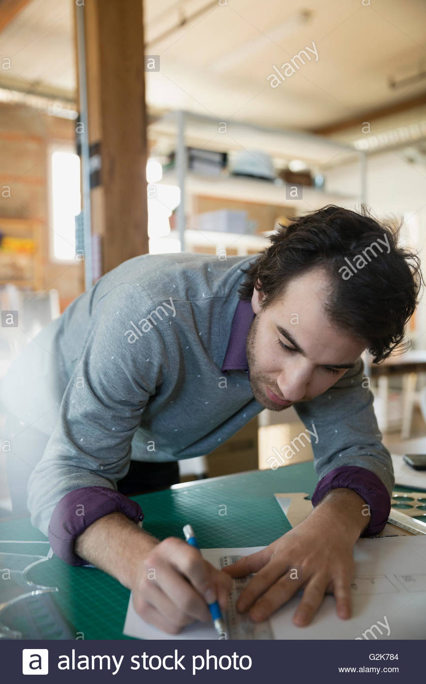 Designer using ruler and bradawl blade on cutting mat in office - Stock Image