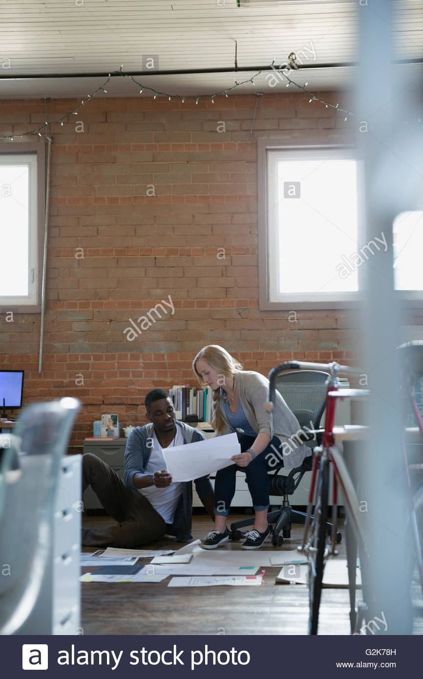 Designers discussing proofs and plans on office floor - Stock Image