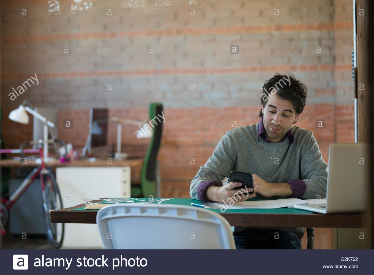 Designer texting with cell phone at desk in office - Stock Image