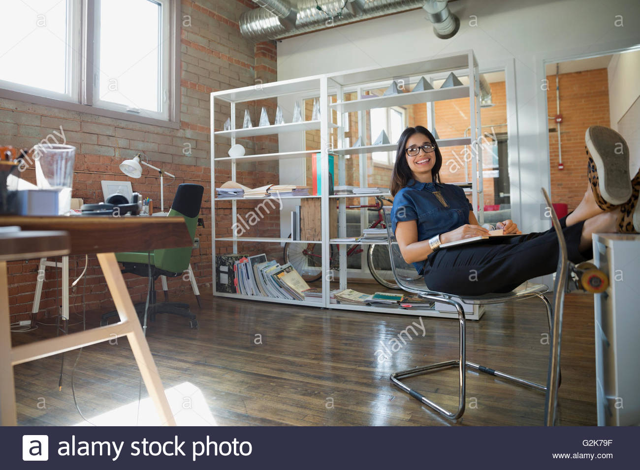 Smiling creative businesswoman with laptop and feet up in office - Stock Image