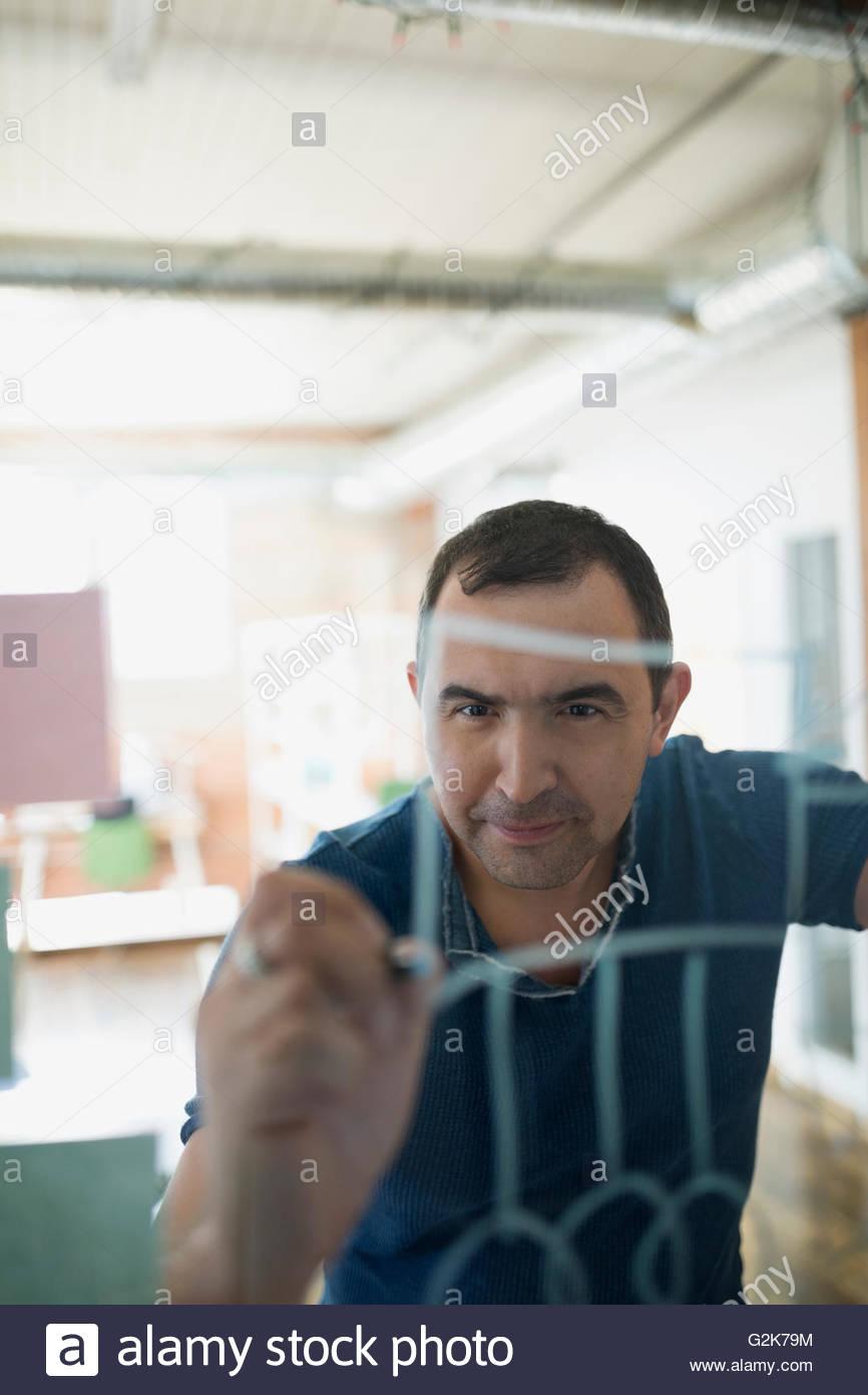 Creative businessman writing on glass - Stock Image