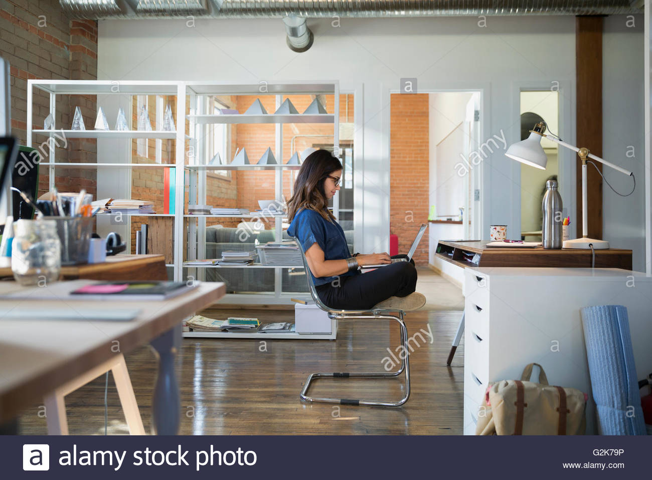Creative businesswoman using laptop cross-legged in office - Stock Image