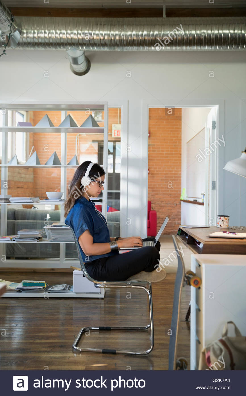 Creative businesswoman with headphones using laptop cross-legged in office - Stock Image