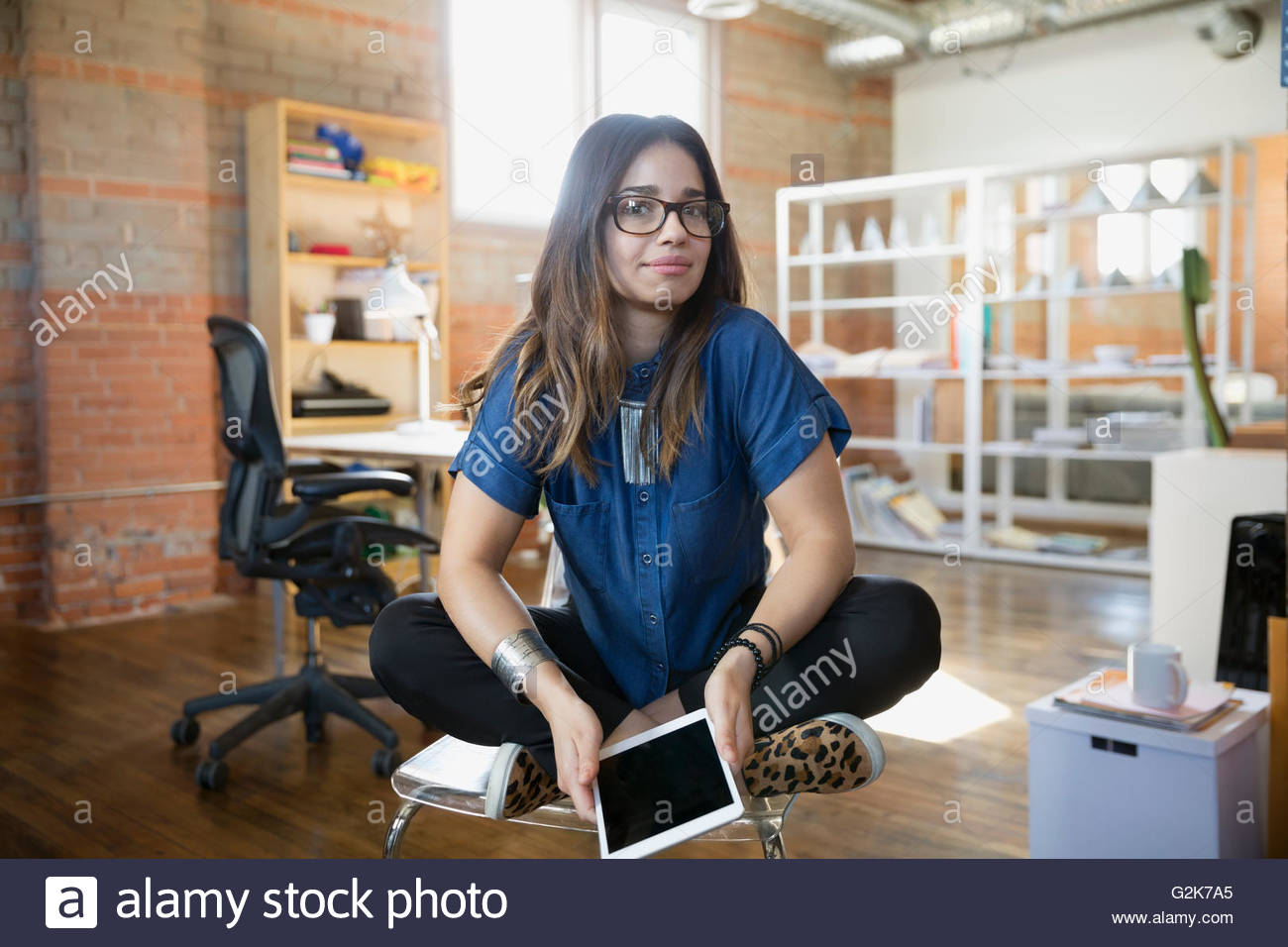 Portrait creative businesswoman cross-legged with digital tablet in office - Stock Image