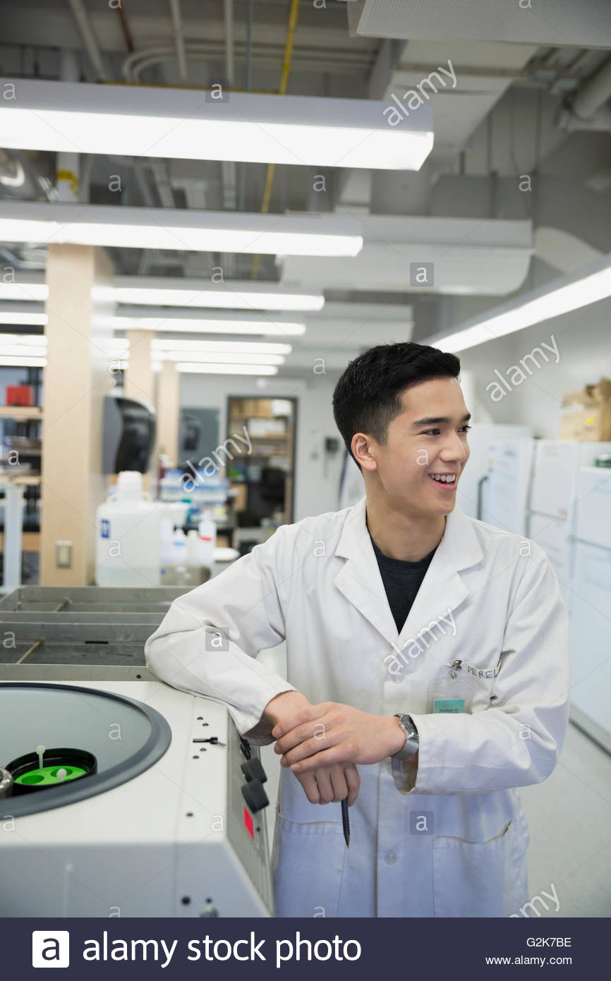 Smiling scientist at centrifuge looking away in laboratory - Stock Image