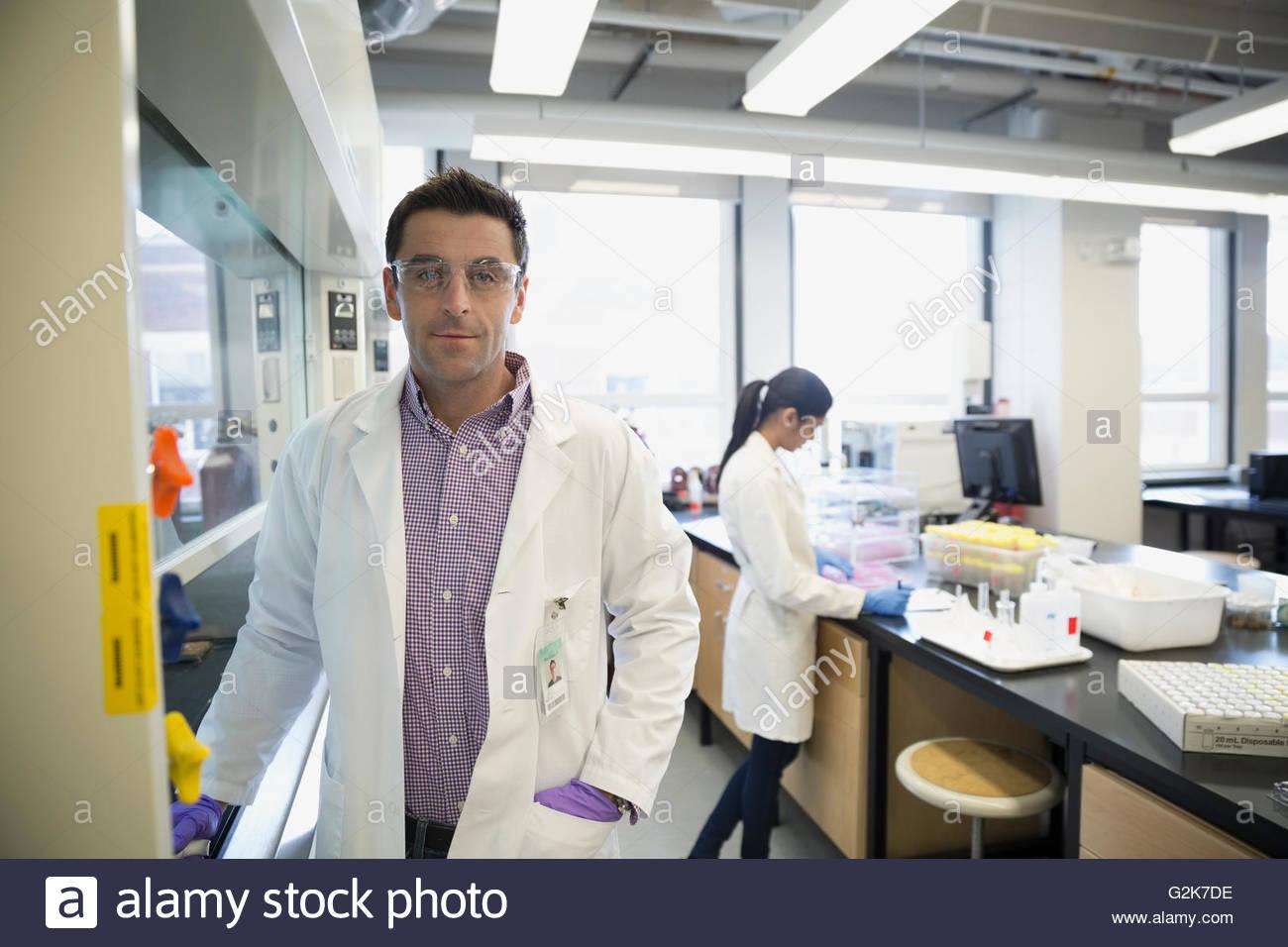 Portrait confident scientist at fume hood in laboratory - Stock Image