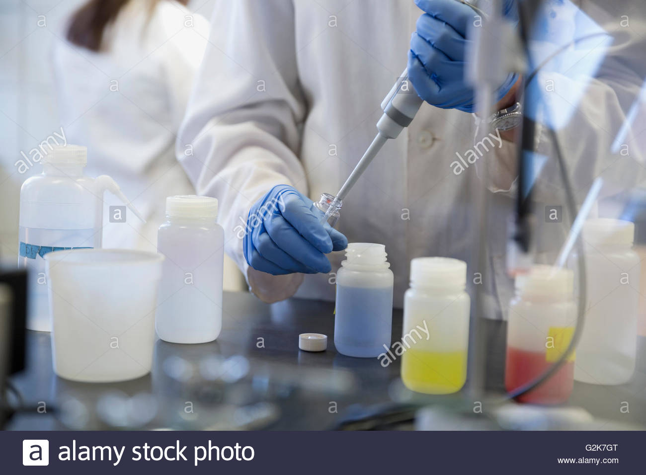 Scientist using pipette to extract liquid in laboratory - Stock Image