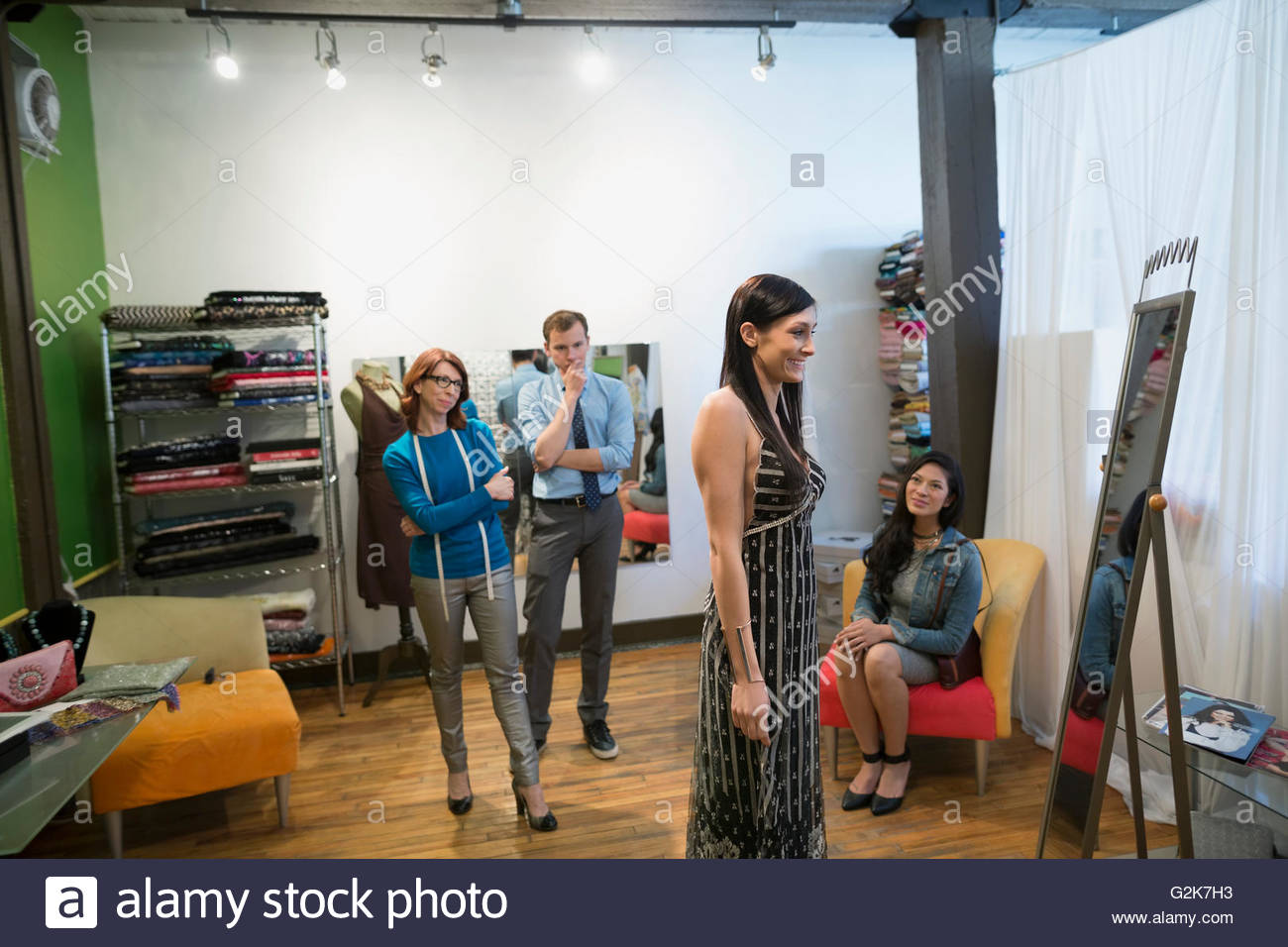 Dressmakers watching customer trying on dress - Stock Image