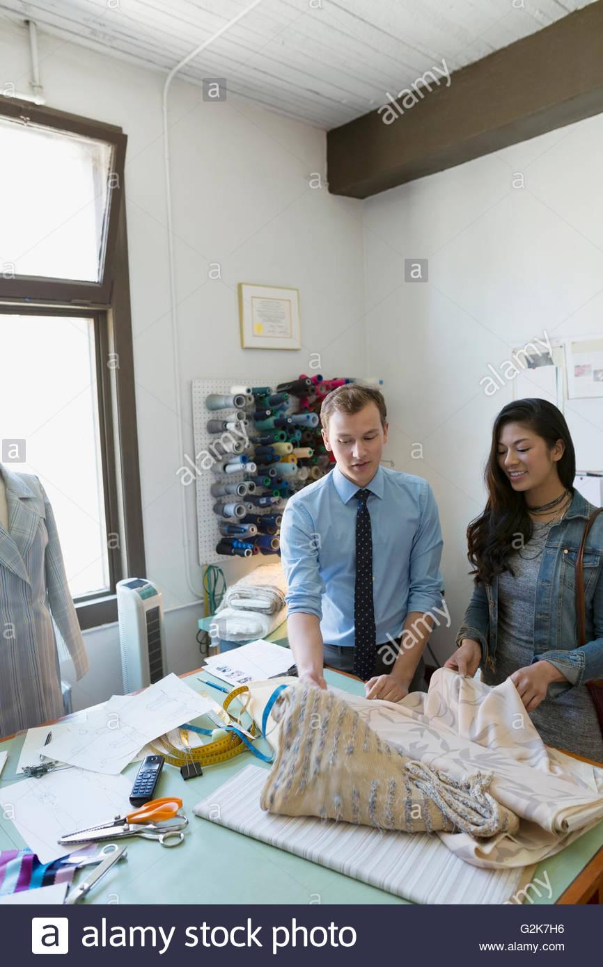 Dressmaker showing customer fabric at workbench - Stock Image