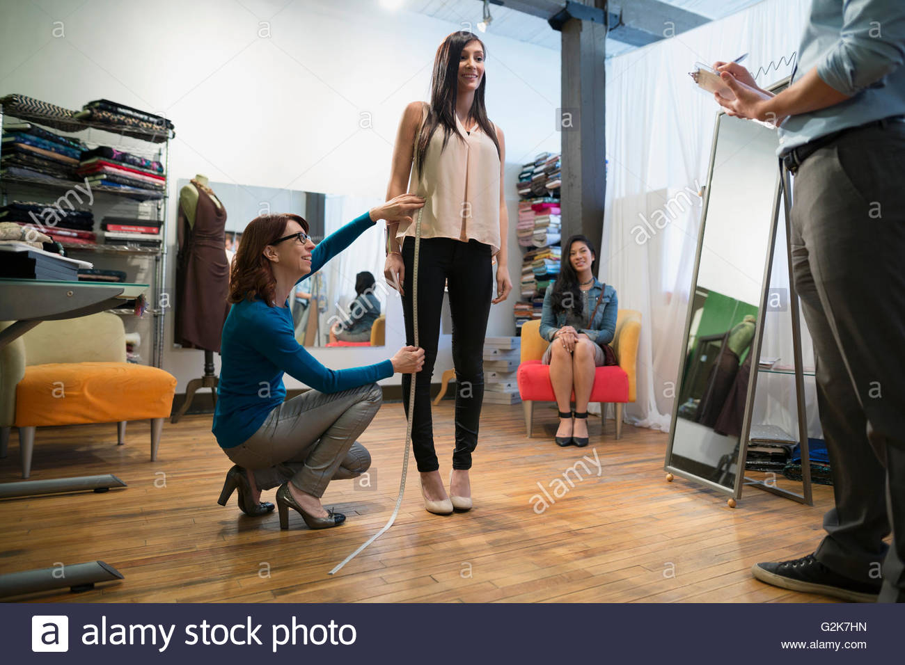 Dressmaker measuring woman - Stock Image