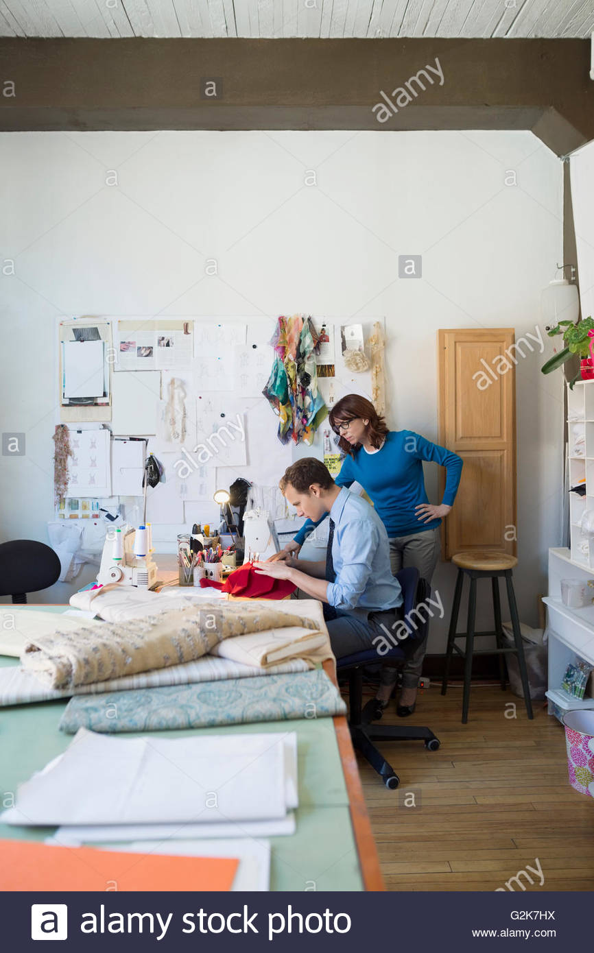 Dressmakers using sewing machine at workbench - Stock Image