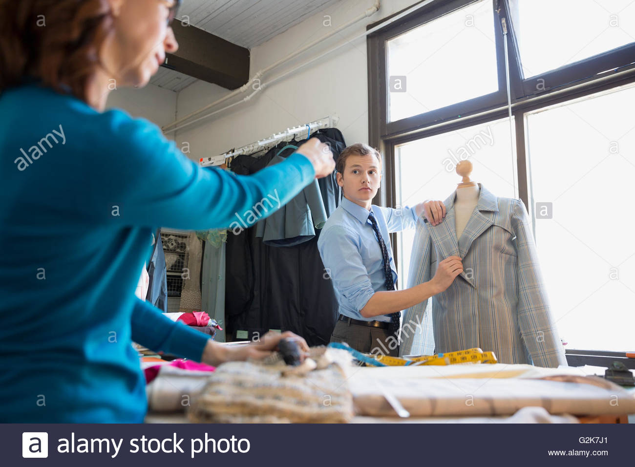 Dressmakers discussing suit on dressmakers model - Stock Image