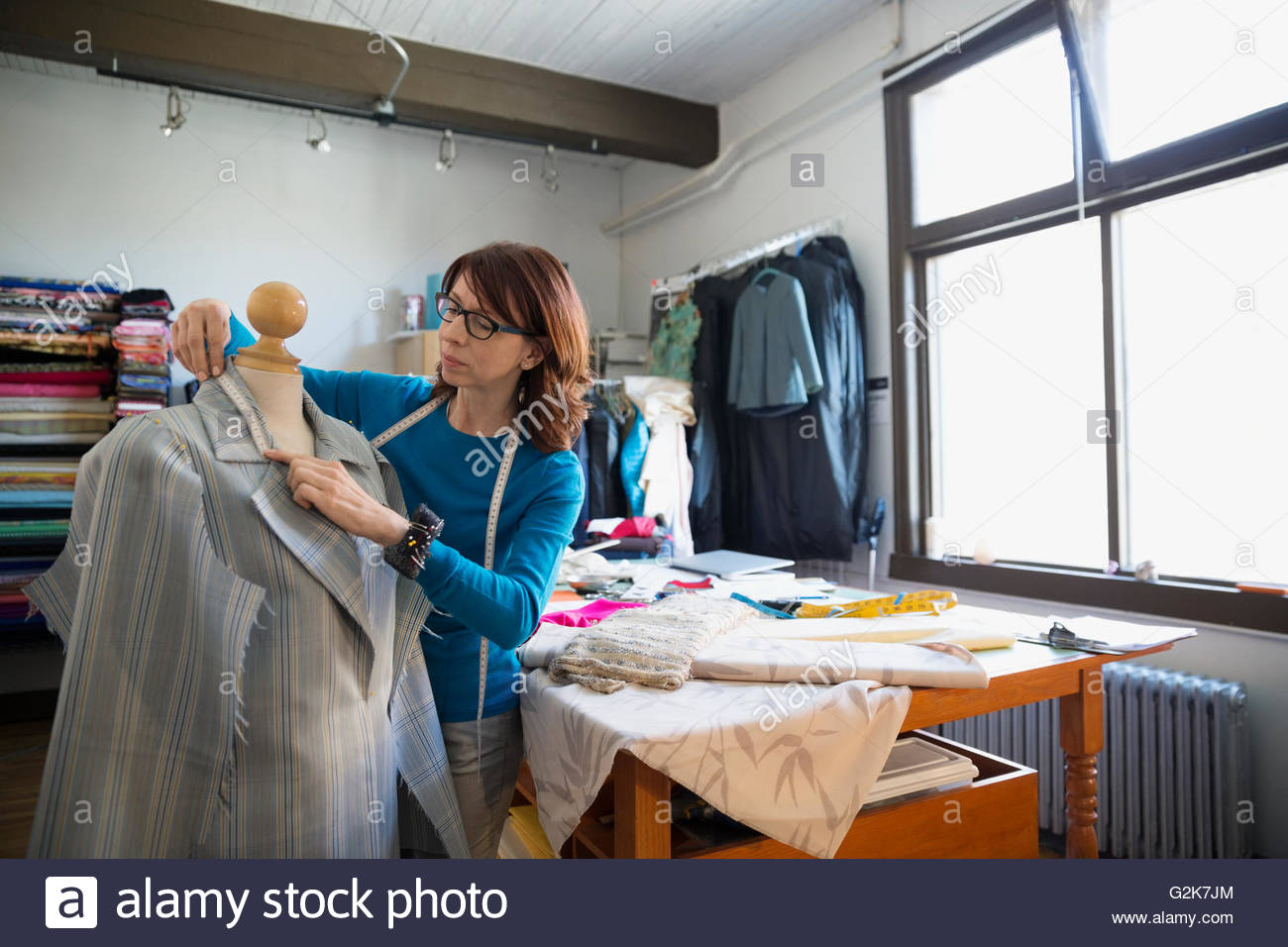 Dressmaker measuring suit on dressmakers model - Stock Image