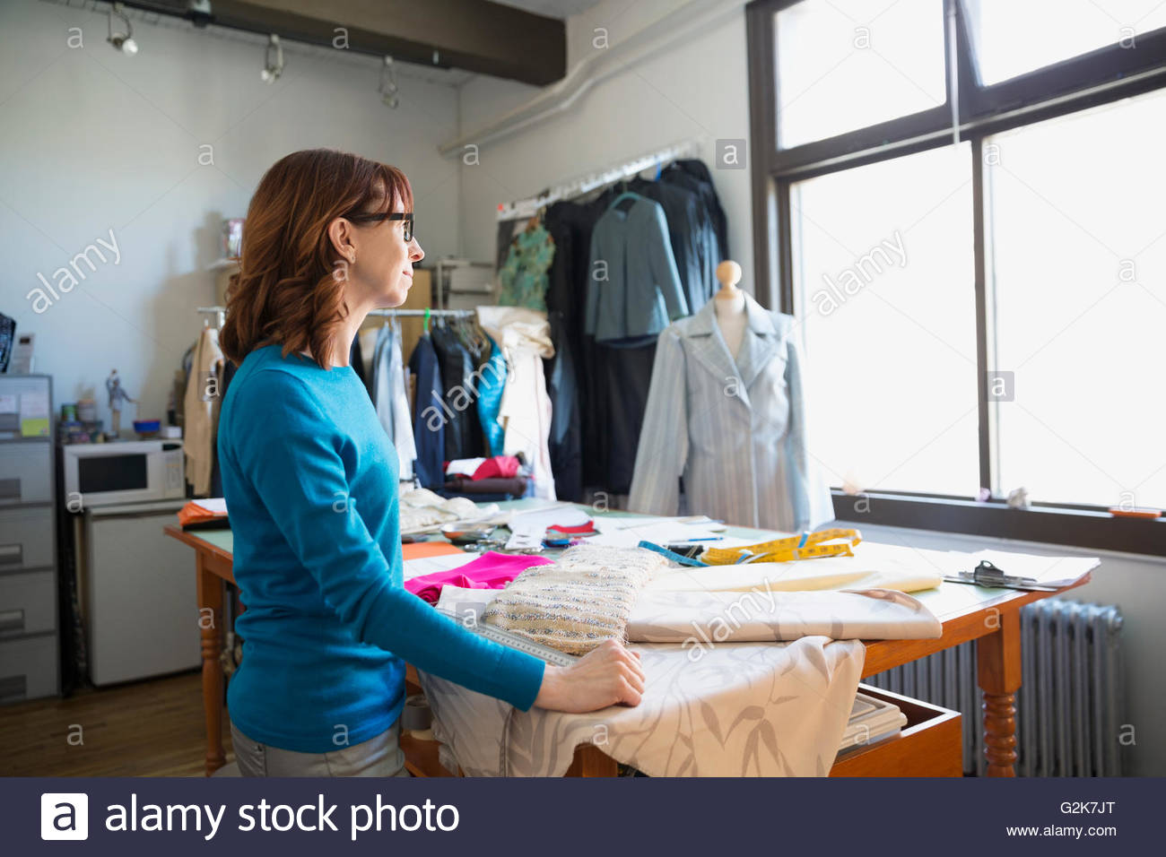 Pensive dressmaker looking through window at workbench - Stock Image