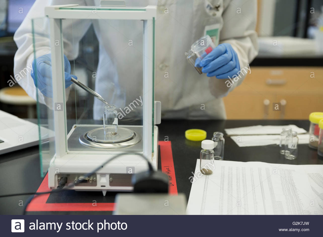 Scientist placing specimen in laboratory scale - Stock Image