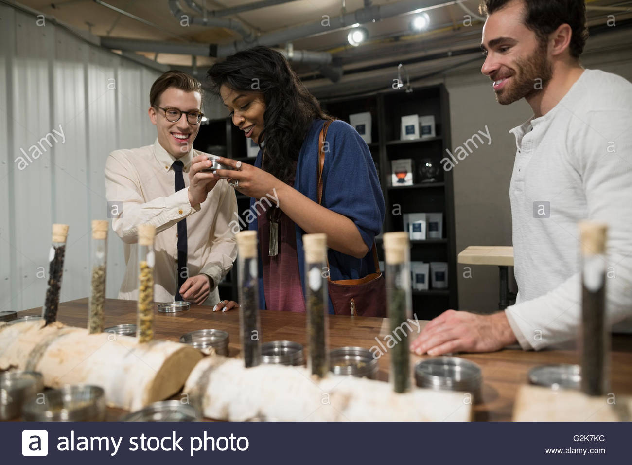 Tea shop owner showing tea to customers - Stock Image