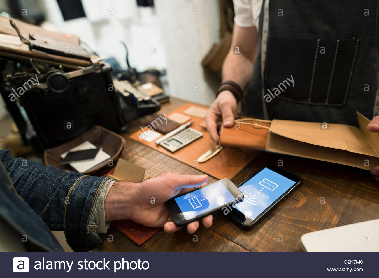 Customer using contactless payment in leather shop - Stock Image