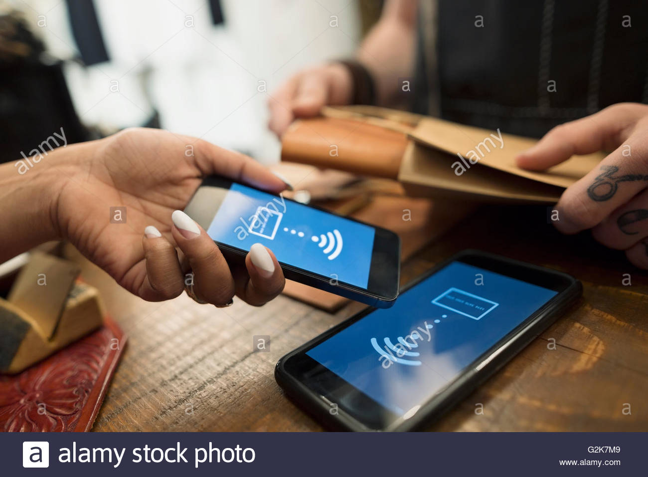 Close up customer using contactless payment in leather shop - Stock Image