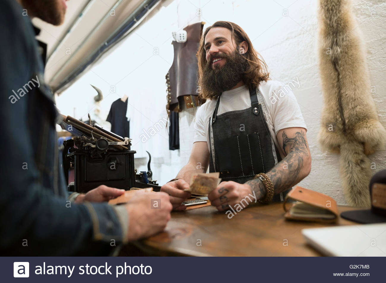 Customer paying leather shop owner - Stock Image